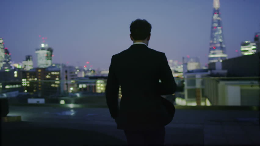 4k / Ultra HD version Successful businessman alone with his thoughts looks out over the view of the London city skyline at night. Shot on RED Epic | Shutterstock HD Video #14004941