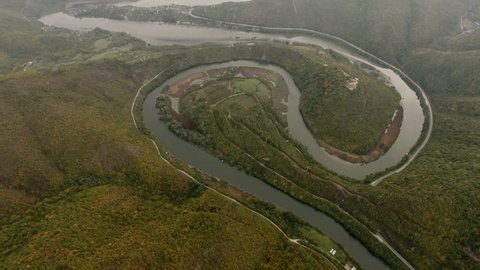 Aerial shot. Flight over a meandering river in the mountain valley.