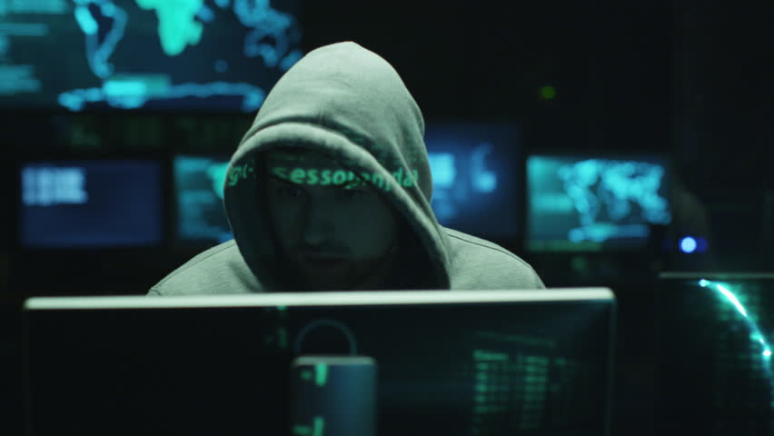 Male hacker working on a computer while green code characters reflect on his face in a dark office room. Shot on RED Cinema Camera in 4K (UHD). | Shutterstock HD Video #14019065