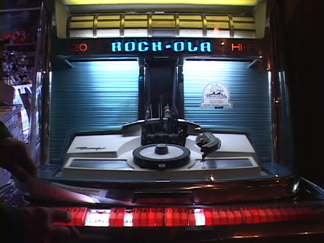 A 45 rpm record is played on an old fashioned jukebox.