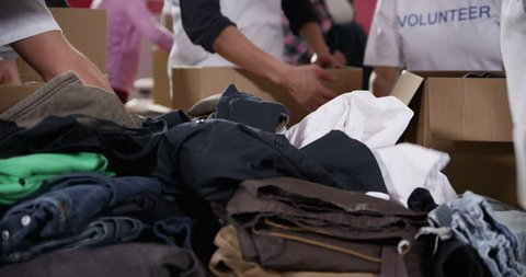 4k / Ultra HD version Charity volunteers and community members chat amongst themselves as they sort through piles of donations of food and clothing. Shot on RED Epic