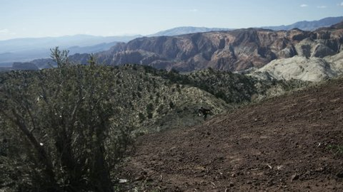slow motion man running up steep trail in desert