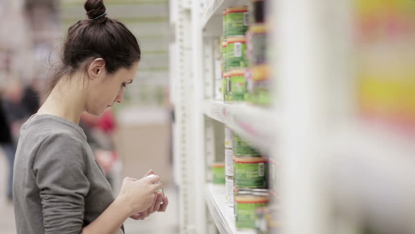 Young woman chooses canned food in the store | Shutterstock HD Video #14051144