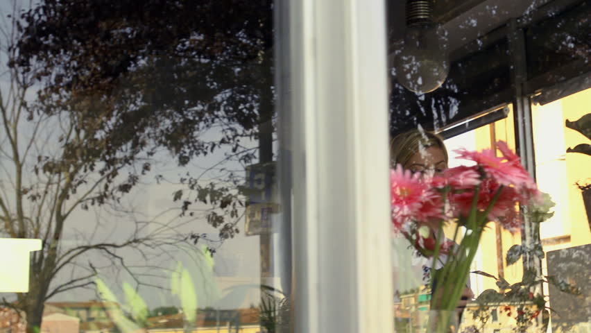 Businesswoman in her own flower shop, preparing bouquet and holding white roses. Dolly shot