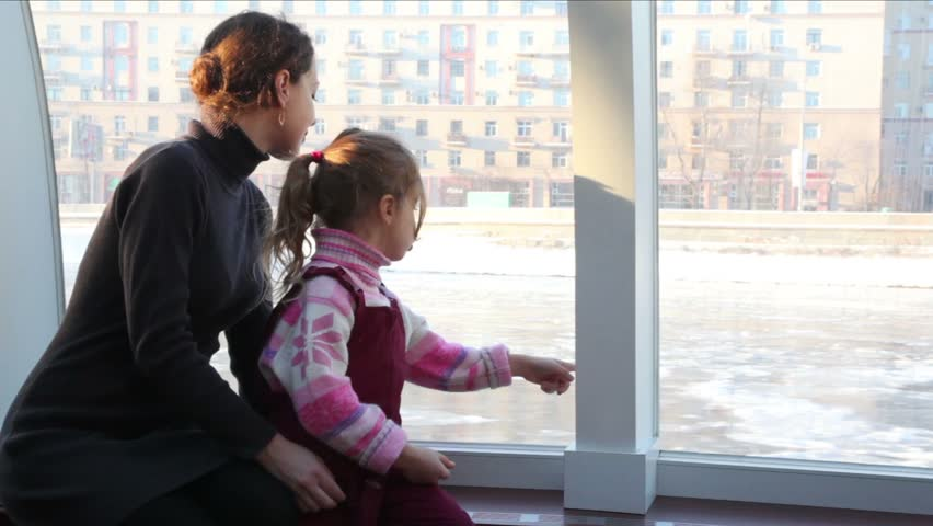 Mother and daughter sit inside ship floating down river in winter  | Shutterstock HD Video #1407424