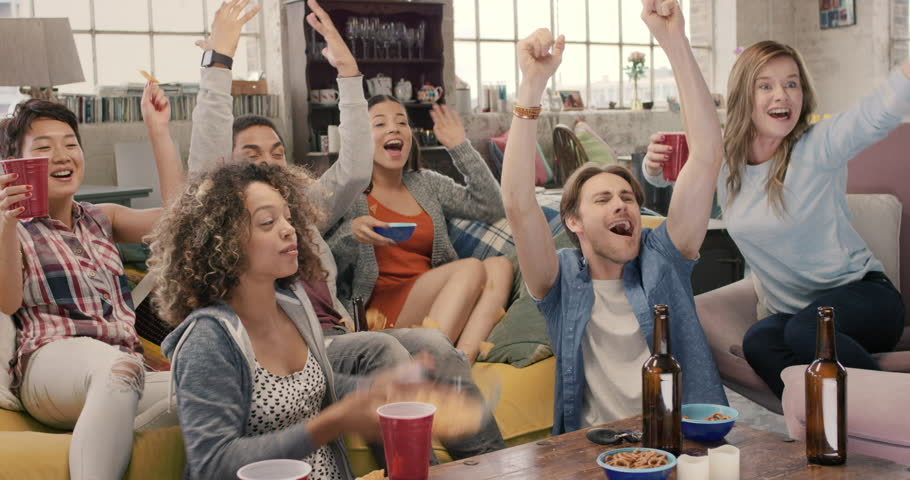 Happy diverse group of student sports fans throwing arms up in excitement celebrating goal watching sports event on TV together bonding as friends eating snacks drinking beer | Shutterstock HD Video #14075132