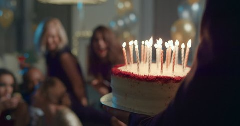 Beautiful woman shares birthday celebration with sexy friends gathered blowing out candles on red velvet cake