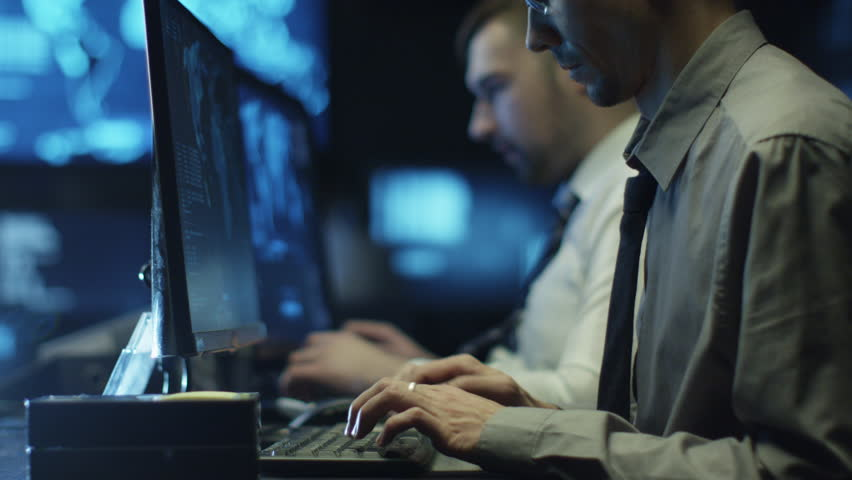 Two IT programmers are working on computer in a dark office room filled with display screens. Shot on RED Cinema Camera in 4K (UHD).