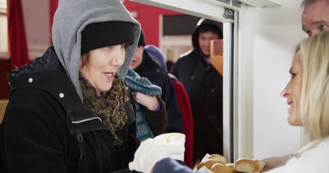 4k / Ultra HD version Friendly voluntary workers of mixed ages and ethnicity are serving hot soup and bread to a waiting line of homeless and needy people. Shot on RED Epic