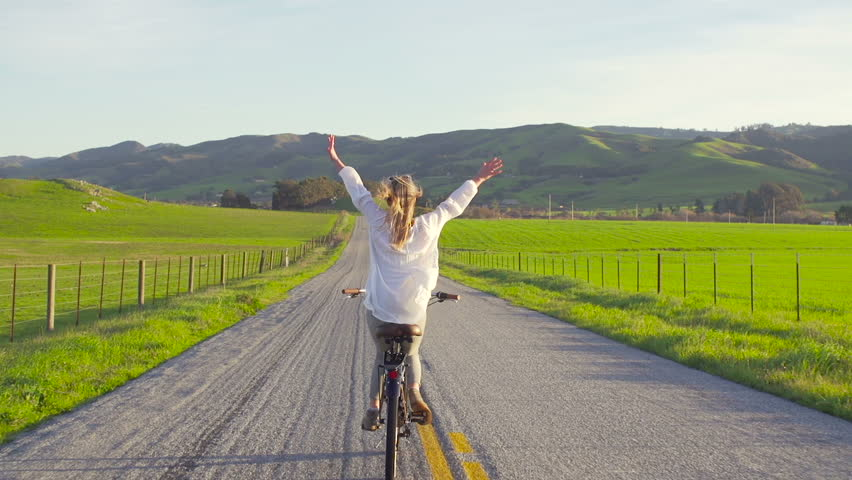 Girl Riding Bike Down Country Road At Sunset With Hands Up In Air  | Shutterstock HD Video #14112818