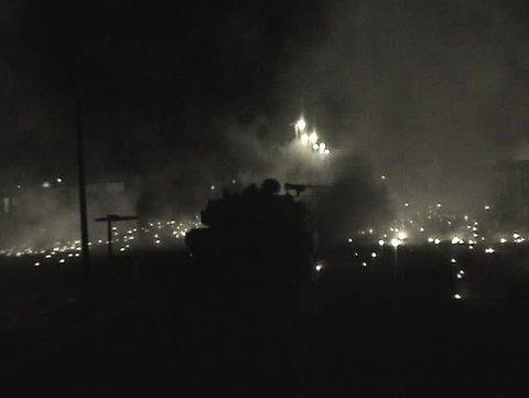 Abrams tanks fire into an Iraqi village.