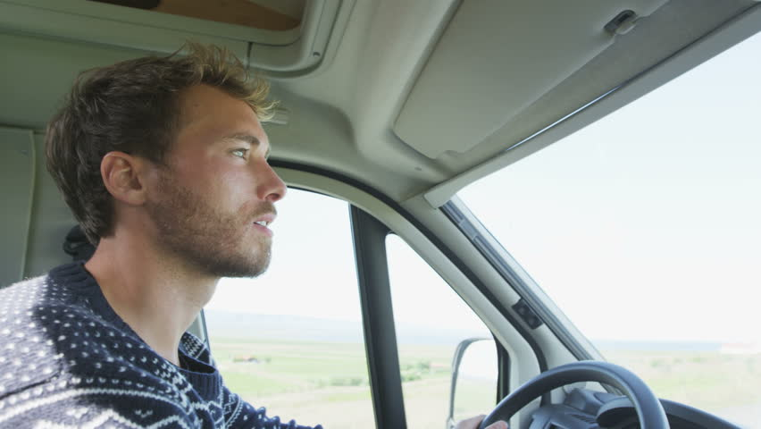 Young man driving mobile home car. Side view portrait of smiling male on roadtrip. Handsome man is concentrating while driving automobile motorhome.