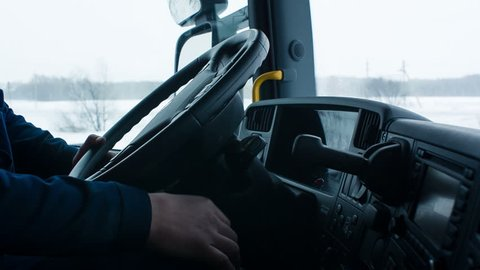 The driver starts a truck, then removes the handbrake and starts to move in a comfortable cabin. He goes on snow-covered road. Worker turns steering wheel of truck. Snow