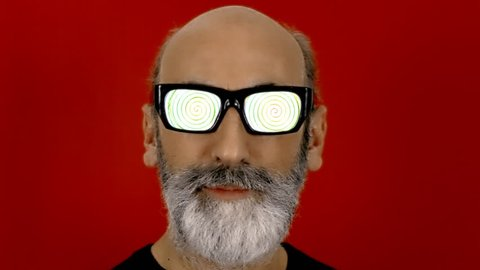 An old man with hypnotic glasses, looking at the viewer while a spiral animation runs into his eyeglasses.
