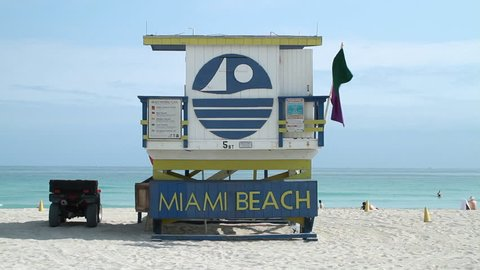 Miami, FL - January, 2012: Stationary establishing shot of Miami Beach Lifeguard tower on the beach. Day. Blue sky ad small waves.