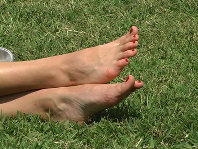 Close-up of a beautiful blonde relaxing in a grassy park. Shot begins with a close-up of her feet and pans left, revealing her shoes on the ground behind her legs. Tilts up to reveal her face.