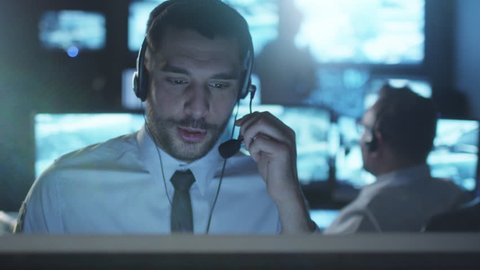 Technical support specialist is talking on a headset while working on a computer in a dark monitoring room filled with display screens. Shot on RED Cinema Camera in 4K (UHD).