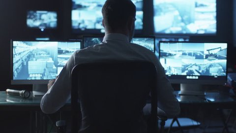 Security officer is drinking coffee while working on a computer in a dark monitoring room filled with display screens. Shot on RED Cinema Camera in 4K (UHD).