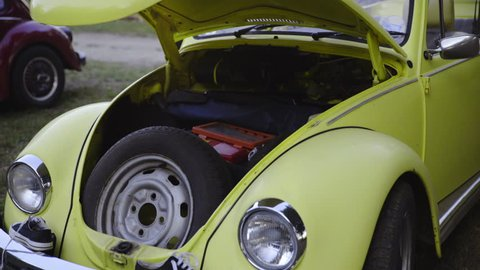 Retro car spare tire under the hood 4K. Zoom on yellow old beetle car with spare tire and tools under front bonnet and two big front lights beside.
