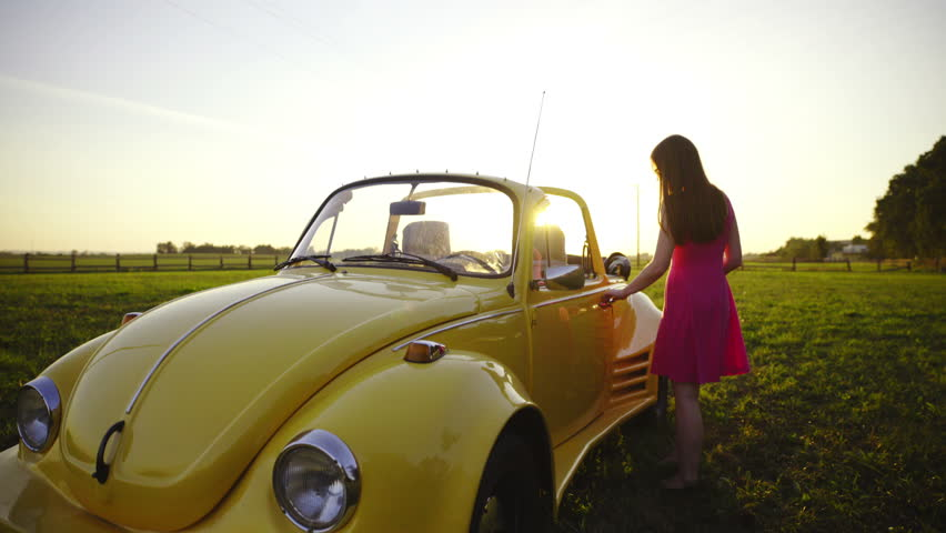 Attractive woman sit inside a beetle at sunset 4K. Beautiful female person in purple dress walk beside a vintage yellow beetle and sit inside. Sunset shining from background.