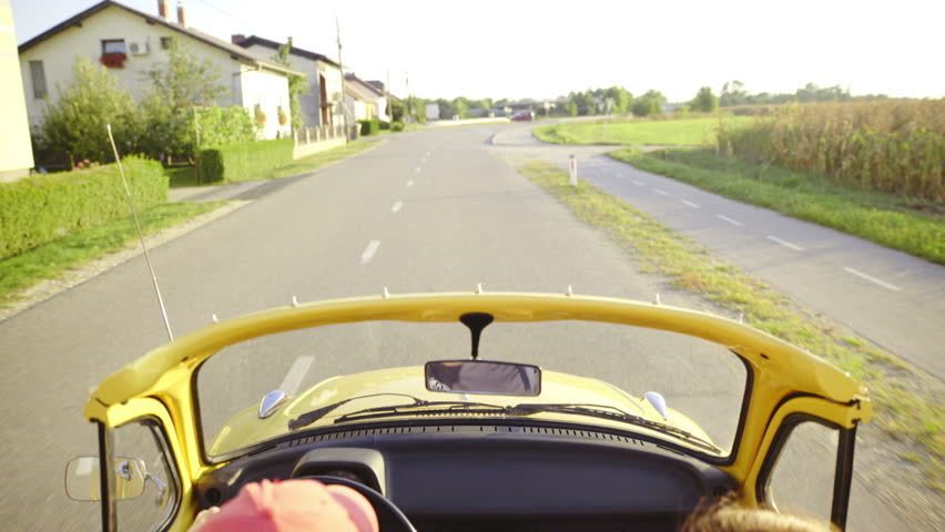 Cabriolet vintage car driving on road 4K. Above the car view of yellow car driving over a bridge in nature. Very bumpy ride in vintage vehicle.