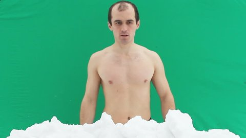Young man with naked torso doing bumps in the snow on a green background