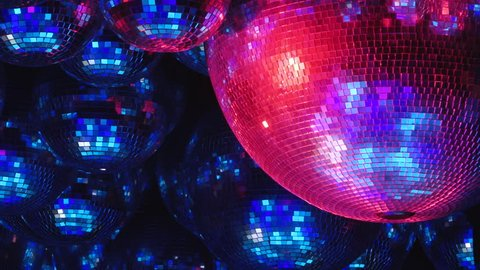 Mirror balls reflect rays of colored lights. Colorful reflective disco mirror ball with glinting highlights spinning slowly on a blurry colored background in disco club. The light show at night.