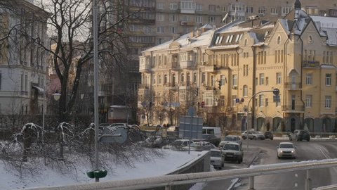 People Are Walking by the Street at Vintage Brown-Blocked Building near Kievo-Pecherska Lavra, view from a bridge, people are walking by street under the bridge, wintery cityscape, cars are driven by