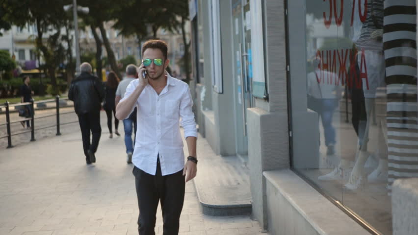 . Young man wearing sunglasses and walking through the city center and talking on telephone. Urban male in his 20s.  | Shutterstock HD Video #14238104