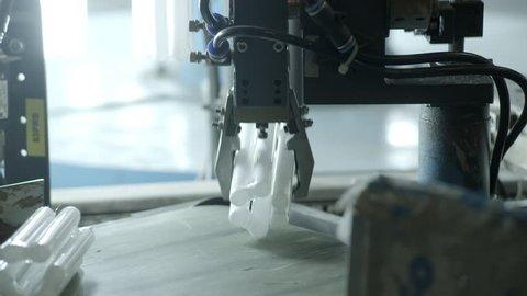 Compact fluorescent lamps put on conveyor belt by robotic arm.