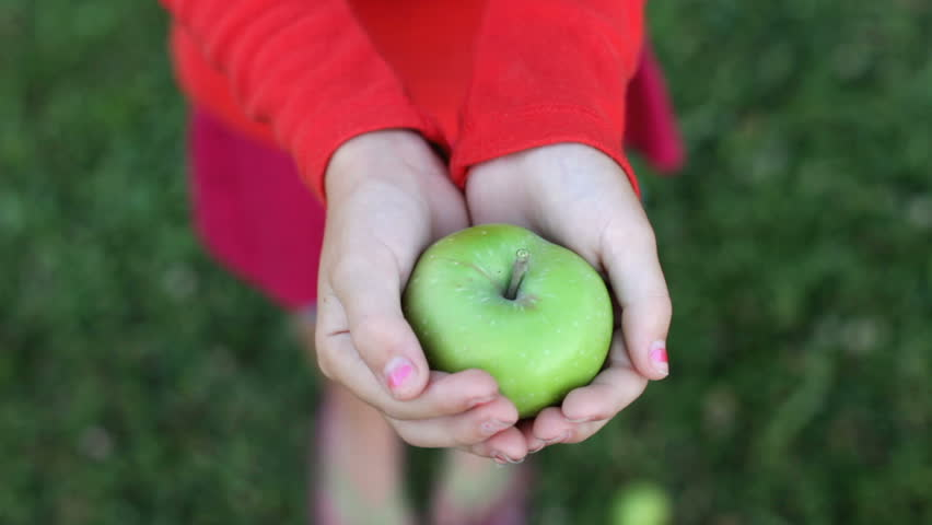 child opening and closing hand with apple