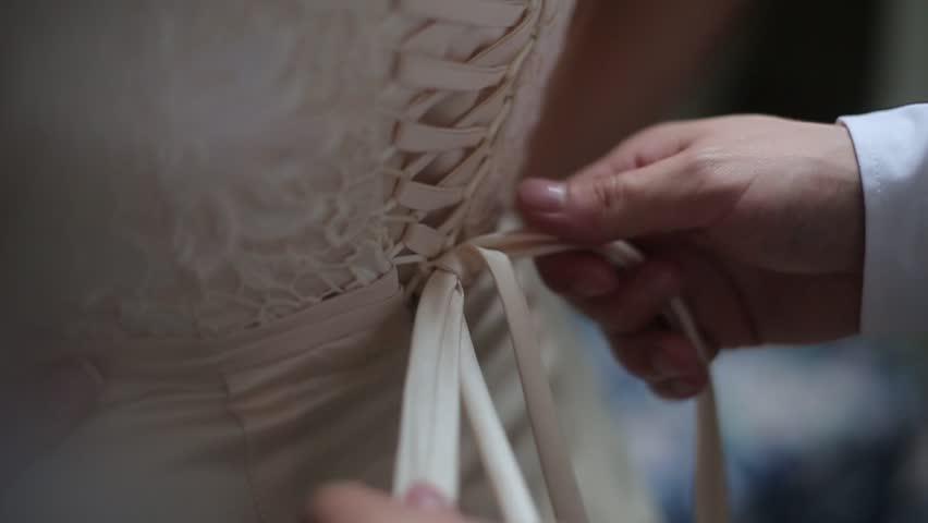 Man tying a corset on the bride's wedding dress.