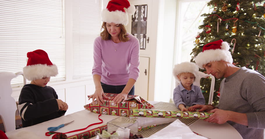 Beautiful white family wrapping presents for the holiday
