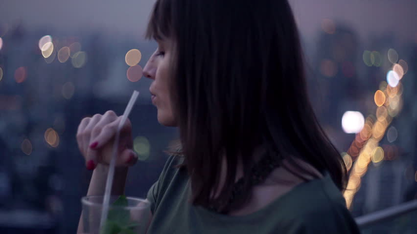 Pensive woman drinking cocktail on terrace in bar at evening