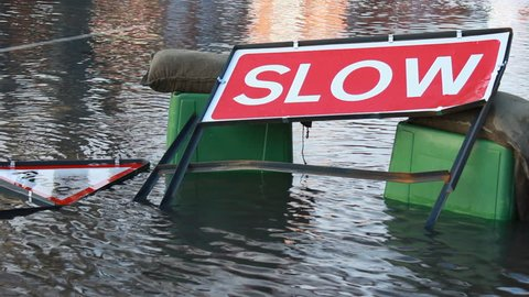 Flood sign and Slow sign in flooded waters. February 2014 - Britain faced unparalleled natural disaster as hurricane-force winds caused damage and transport chaos around the country. Newbury, UK