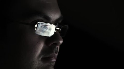 man in glasses watches surfing nude sexy girls on the web net looking at night in a dark room,useful to represent internet easy porn accessibility and social issue