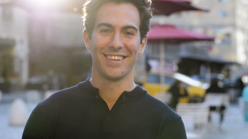 Young man smiling and looking at camera. Portrait of a happy handsome young man in a urban street. Close up face of young cool trendy man looking at camera at sunset.