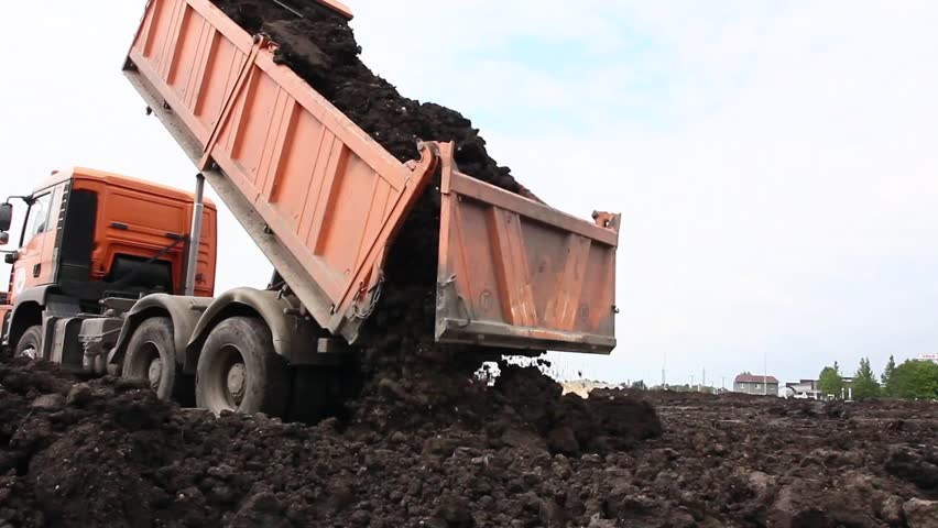 Many dump trucks are unloading soil at the same pile. Dumper trucks are unloading soil or sand at construction site.