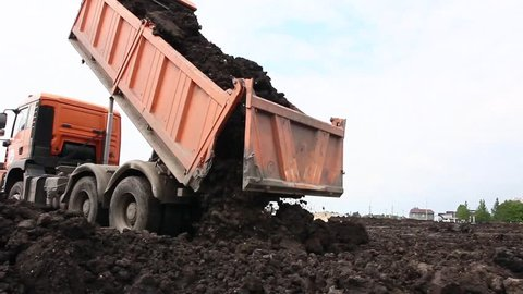 Many dump trucks are unloading soil at the same pile.