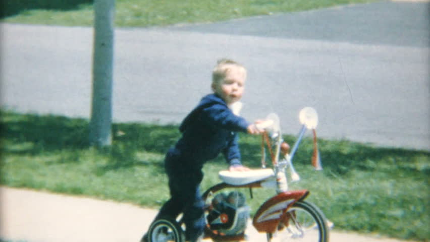 AKRON, OHIO, JULY 15, 1967: A cute little boy crashes his tricycle on the sidewalk in the summer of 1967.