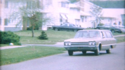 AKRON, OHIO, JULY 15, 1967: A mom drives her classic vintage 1967 Dodge Station wagon home from a shopping trip.