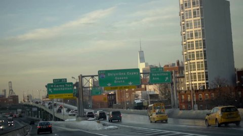 NEW YORK - JAN 25, 2016: cars driving on FDR Drive at sunset with Freedom Tower skyscraper and signs in background in winter NYC. The city's highways provide inter-borough travel.
