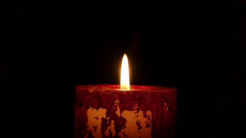 Big And Tall Red Candle Stands In A Dark Room And Lit