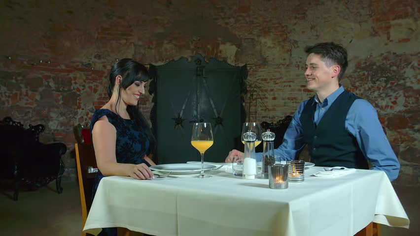 In this video, we can see a young couple toasting with orange juice before a romantic dinner in a restaurant. Wide-angle shot.