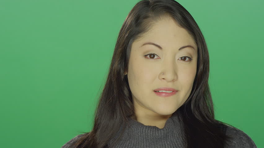 Beautiful young asian woman smiling and flirting, on a green screen studio background | Shutterstock HD Video #14360524