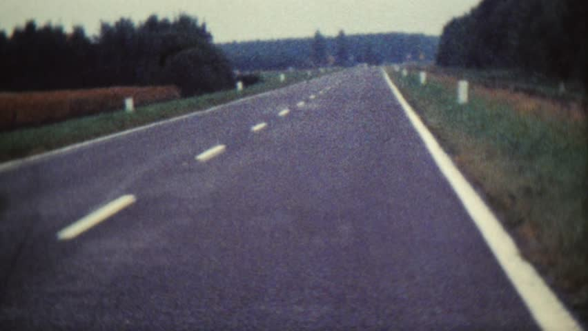 CIRCA 1968: Vintage 8mm film of a highway with old cars and sailing boats