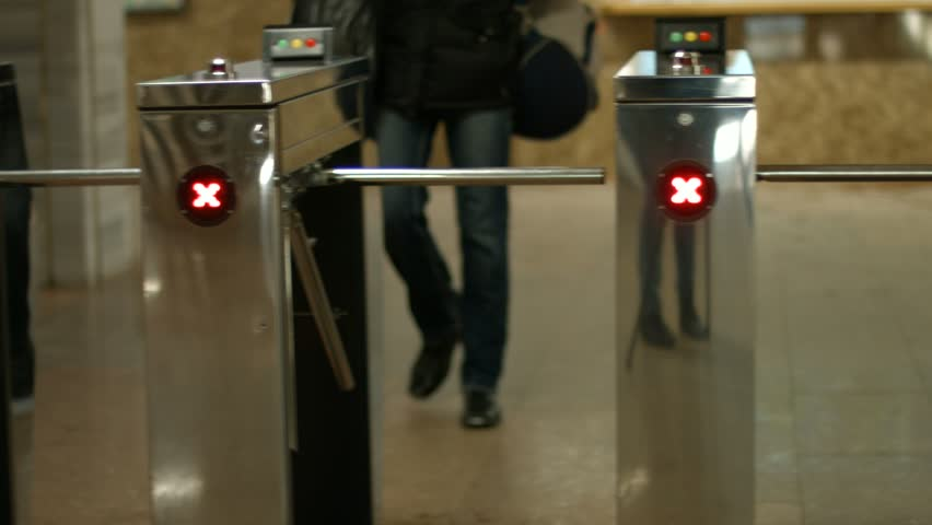 People pass through the turnstiles. Check point. Turnstiles in the subway.