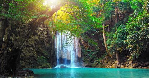 Sunshine and beautiful waterfall flows to wild pond in rain forest of Thailand