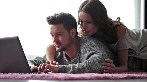 Young couple with tablet lying prone on carpet, wi-fi technology