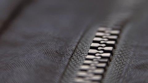 Hand unzipped and fasten black plastic zipper on black jacket. Closeup. Shallow depth of field